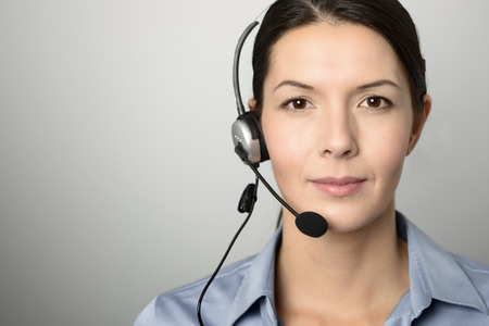 telemarketer: Attractive female call center operator, client services assistant or telemarketer wearing a headset looking at the camera with a charming friendly smile, on grey with copy space Stock Photo