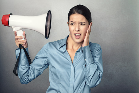 overpowering: Young woman holding a megaphone to her head and clutching her ear with an aggrieved expression at the loudness of the sound so close to her, conceptual image isolated on grey Stock Photo