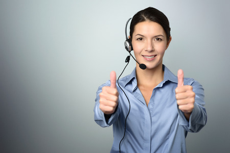 Attractive female call center operator, client services assistant or telemarketer wearing a headset looking at the camera and giving a thumbs up, on grey with copy space photo