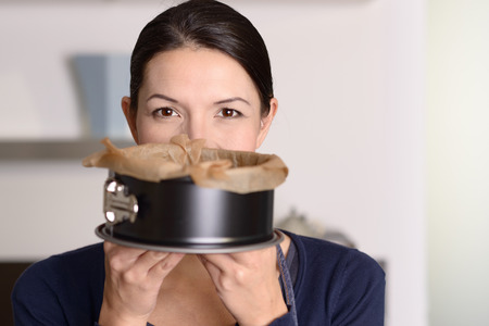 baking oven: Smiling woman holding up a freshly baked cake in a baking tin which she has just removed from the oven, concealing her lower face with smiling eyes above Stock Photo