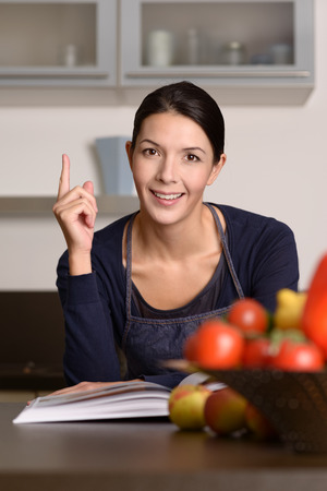 emphasizing: Thoughtful Young Woman Wearing Apron Sitting at the Kitchen with Recipe Book, Emphasizing Positive Hand Sign.