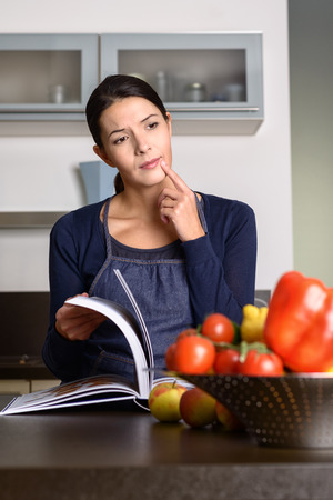 Thougthful middle-aged Woman Wearing Apron reading a Recipe Book at the Kitchen counter