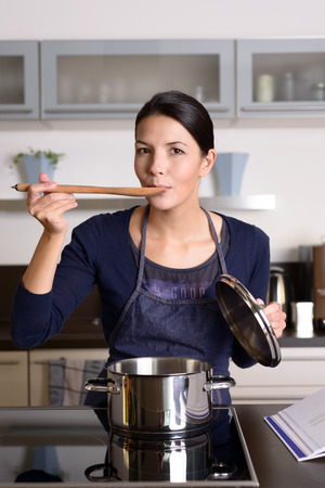 hob: Young housewife tasting her cooking as she prepares the dinner in her kitchen sampling directly from the pot on the hob with a wooden spoon as she looks at the camera Stock Photo