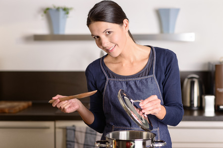 Young woman cooking the food for dinner over the stove in her kitchen standing holding the lid of a stainless steel saucepan and wooden ladle as she smiles at the camera Foto de archivo