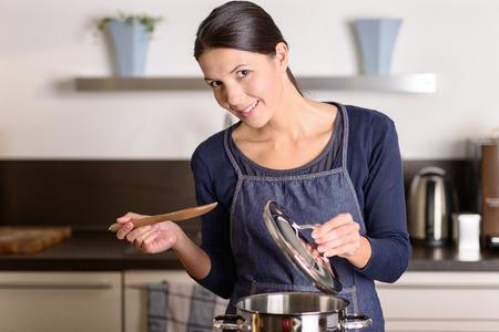 Junge Frau kocht das Essen für das Abendessen über dem Herd in ihrer Küche Standing halten den Deckel aus einem rostfreien Stahl Topf und Holzlöffel, während sie in die Kamera lächelt
