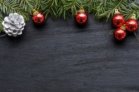 seasonal greeting: Christmas background with colorful red baubles, a silver decorative pine cone and green pine branches over a textured grey background with copyspace for your seasonal greeting