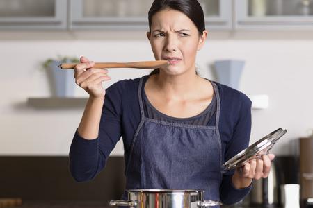 Aantrekkelijke jonge vrouwelijke kok die zich op de kookplaat in haar schort haar eten te proeven