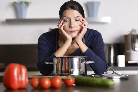 eyeing: Unmotivated attractive young woman preparing the dinner leaning on the hob eyeing the fresh vegetables with a listless glum expression as she stands in her kitchen in an apron Stock Photo