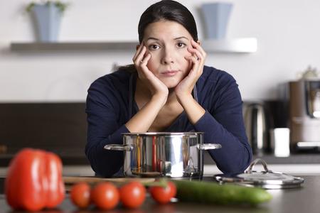 Ongemotiveerd aantrekkelijke jonge vrouw de voorbereiding van het diner leunend op de kookplaat bekeek de camera met een lusteloze somber uitdrukking als ze staat in haar keuken in een schort