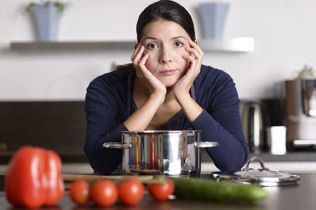 glum: Unmotivated attractive young woman preparing the dinner leaning on the hob eyeing the camera with a listless glum expression as she stands in her kitchen in an apron