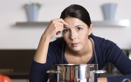 listless: Unmotivated attractive young woman preparing the dinner leaning on the hob eyeing the camera with a listless glum expression as she stands in her kitchen in an apron