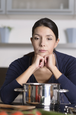 glum: Unmotivated attractive young woman preparing the dinner leaning on the hob eyeing the fresh vegetables with a listless glum expression as she stands in her kitchen in an apron Stock Photo