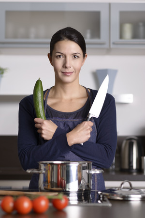 knife tomato: Happy young woman posing in her kitchen with her arms crossed holding a knife and fresh cucumber as she prepares a healthy dinner, frontal view standing at the stove Stock Photo
