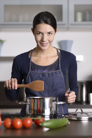 Happy friendly young housewife cooking dinner standing at the hob holding a wooden spoon over a saucepan as she prepares the fresh vegetables for dinner while giving the camera a lovely smile