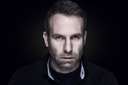 카메라, 어두운 변덕 머리와 어깨 초상화를 직접보고 어두운 심각한 표정으로 잘 생긴 유엔 중간 남자