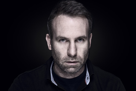 inscrutable: Handsome unshaven middle-aged man with a sombre serious expression looking directly at the camera , dark moody head and shoulders portrait