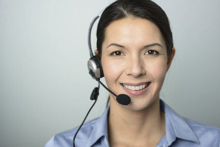Attractive female call center operator, client services assistant or telemarketer wearing a headset looking at the camera with a charming friendly smile, on grey with copy space photo