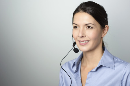call center female: Attractive female call center operator, client services assistant or telemarketer wearing a headset looking at the camera with a charming friendly smile, on grey with copy space Stock Photo