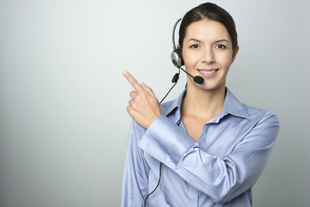 advertising space: Smiling attractive young businesswoman with a headset pointing with her finger towards blank copyspace on a graduated grey background