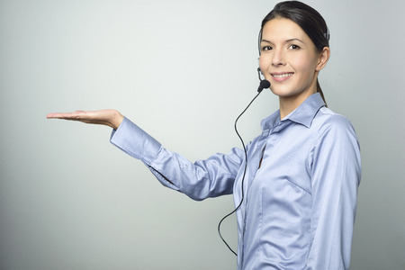 extending: Smiling attractive, friendly woman doing telemarketing or a promotion wearing a headset and extending her empty palm for your product placement over blank grey copy space