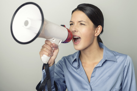 public address: Woman speaking over a megaphone as she makes a public address, participates in a protest or organises a rally or promotion, over grey with copyspace to the side