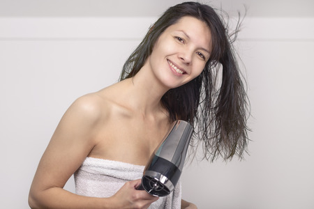 Attractive woman in a towel blow drying her log brown hair with a handheld hairdryer in her bathroom looking at the camera with a warm friendly smile photo