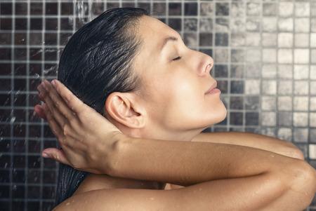 mojada: Mujer atractiva que se lava el pelo en la ducha de enjuagar bajo el chorro de agua con la cabeza echada hacia atrás y los ojos cerrados en un concepto de cuidado del cabello, belleza e higiene