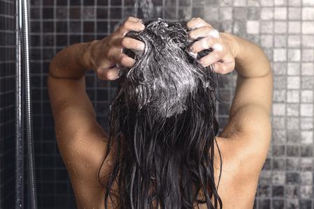 Mujer con champú el pelo largo y castaño bajo una ducha de pie, de espaldas a la cámara de trabajo encima de una espuma bajo el chorro de agua