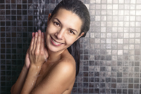 Attractive woman washing her hair in the shower rinsing it off under the spray of water with her head tilted back looking away in a hair care, beauty and hygiene concept