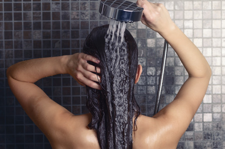 Junge Frau, die ihr langes Haar unter der Dusche stehen mit dem Rücken zur Kamera Abspülen unter dem Wasserstrahl, den Kopf teilweise zur Seite gedreht, über grauen Mosaikfliesen Lizenzfreie Bilder