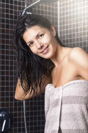 draped: Smiling attractive young woman with wet hair standing in a shower tiled in grey mosaics draped in a towel smiling at the camera in a personal hygiene and beauty concept