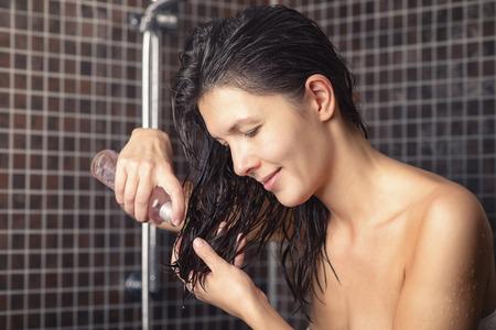 mujeres morenas: Mujer joven a punto de aplicar el aceite de pelo para el pelo reci�n lavado de pie en el cuarto de ba�o en una toalla de la dispensaci�n en la mano de la botella Foto de archivo
