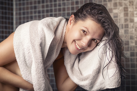 Smiling woman with wet hair standing in a shower with grey mosaic tiles drying herself on a clean white towel in a personal hygiene and beauty concept