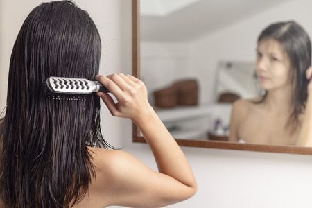 Young woman standing looking at her reflection in the bathroom mirror while brushing her wet hair with a hairbrush after washing it, view from behind