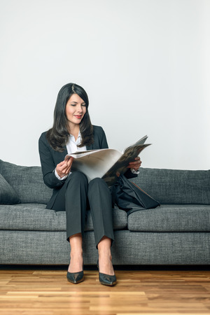 slack: Attractive businesswoman in a stylish slack suit sitting reading a business journal or newspaper on a grey sofa with her briefcase alongside her as she waits for an appointment