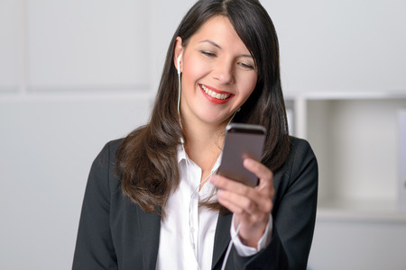 downloaded: Smiling young professional woman listening to music on her MP3 player using earplugs as she happily selects a tune from her downloaded library