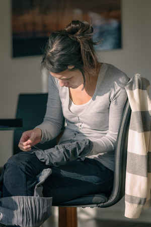 darn: Young housewife or mother stitching darning a pair of jeans trousers Stock Photo