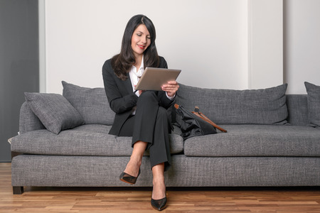 slack: Stylish businesswoman sitting reading a tablet-pc on a grey sofa with her briefcase alongside her as she waits for an appointment or meeting Stock Photo