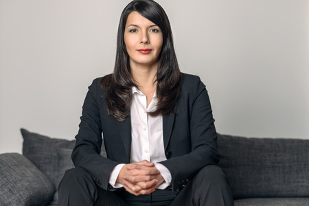 waiting posture: Attractive businesswoman in a slack suit sitting on a sofa looking at the camera with a quiet smile of satisfaction and her hands clasped in front of her Stock Photo