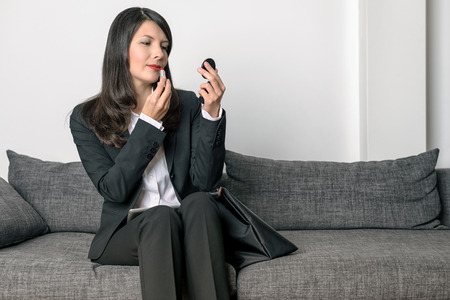 slack: Attractive professional woman in a stylish slack suit sitting on a grey sofa refreshing her lipstick in a compact mirror Stock Photo