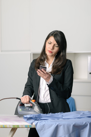 glum: Bored unhappy housewife doing the ironing staring off to the side with a glum expression while simultaneously checking emails on her smart phone Stock Photo