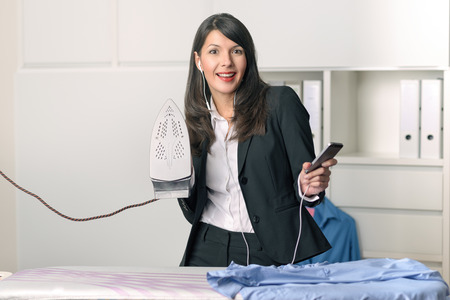 ironing board: Happy housewife standing listening to music on her MP3 player while ironing the shirts at an ironing board with a smile of pleasure and enjoyment on her face