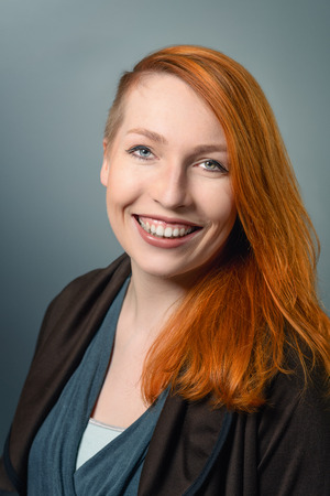 red haired woman: Portrait of Smiling Confident Red Haired Woman Casually Dressed looking at the camera on gray studio background
