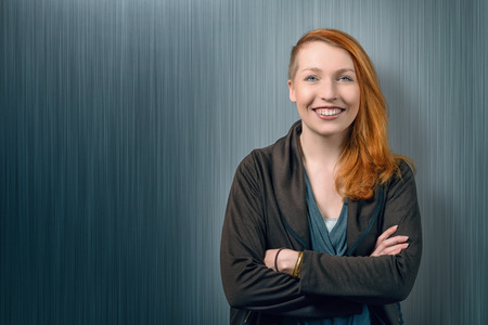 red head woman: Smiling happy pretty red head woman with her long hair over one shoulder in a grey jersey standing with her arms folded against a chalkboard background with copyspace