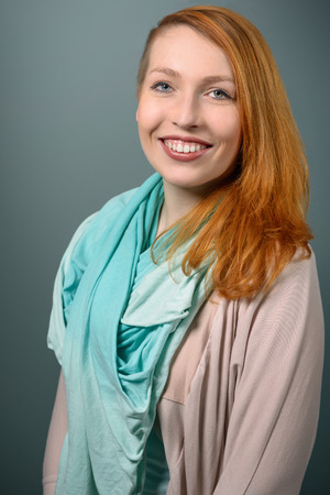 red haired: Close up Portrait of Smiling red haired Woman with Light Blue Green Scarf Looking at the Camera on Gray Background. Stock Photo