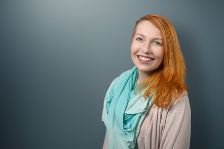 red haired woman: Close up Portrait of Smiling red haired Woman with Light Blue Green Scarf Looking at the Camera on Gray Background. Stock Photo