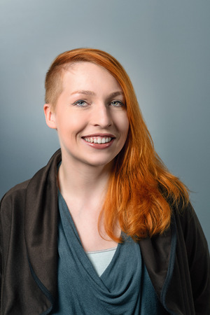 Portrait of Smiling Confident Red Haired Woman with a sidecut hairstyle looking at the camera on gray studio background Stock Photo