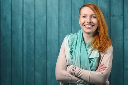 copyspace와 칠판 배경에 대해 접혀 그녀의 팔을 회색 유니폼 서 하나의 어깨 너머로 그녀의 긴 머리를 가진 행복 예쁜 빨간 머리 웃는 여자