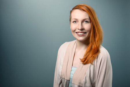 Close up Portrait of Smiling red haired Woman Looking at the Camera on Gray Background.