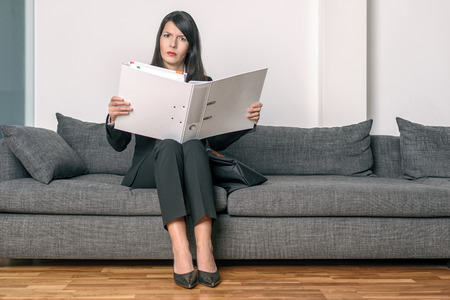 slack: Young businesswoman in a stylish slack suit sitting on a sofa reading her notes or paperwork in an office binder with an expression of concentration